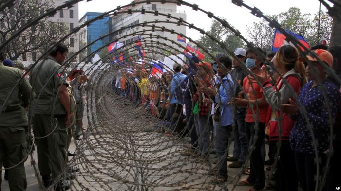 Камбоджійських робітників, які протестують біля будівлі Ради міністрів через низьку зарплатню, відділили від поліції колючим дротом. Пномпень, Камбоджа, 2013 рік.