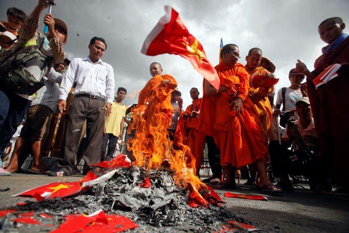Буддійські монахи спалюють паперові в'єтнамські прапори під час протесту біля посольства Соціалістичної Республіки В'єтнам у Пномпені, Камбоджа, 2014 рік